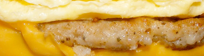 closeup of breakfast sandwich: sausage, egg, cheese....
