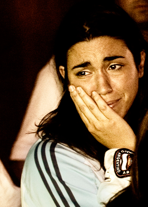 Woman with hand on face near tears wearing jersey of team she supports