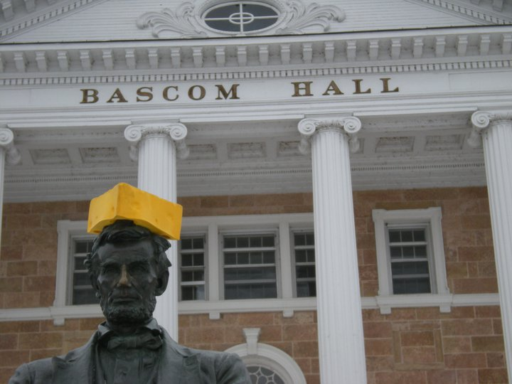Statue of Abraham Lincoln wearing yellow foam cheese hat in front of stone building with white pillars