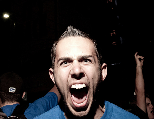 Man with wide open mouth, seemingly screaming, with intense, narrowed eyes