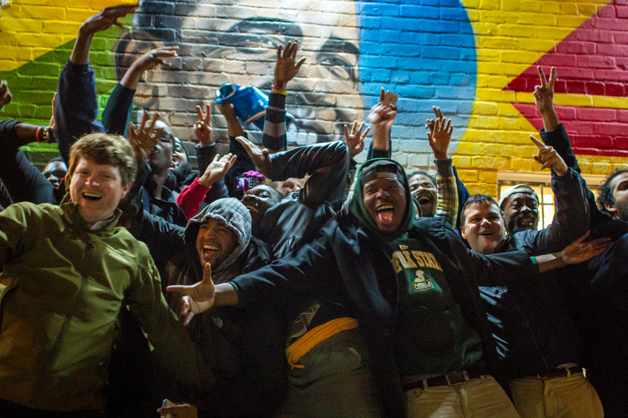 Crowd with raised hands and big smiles energetically leaning together for photo in front of Obama mural