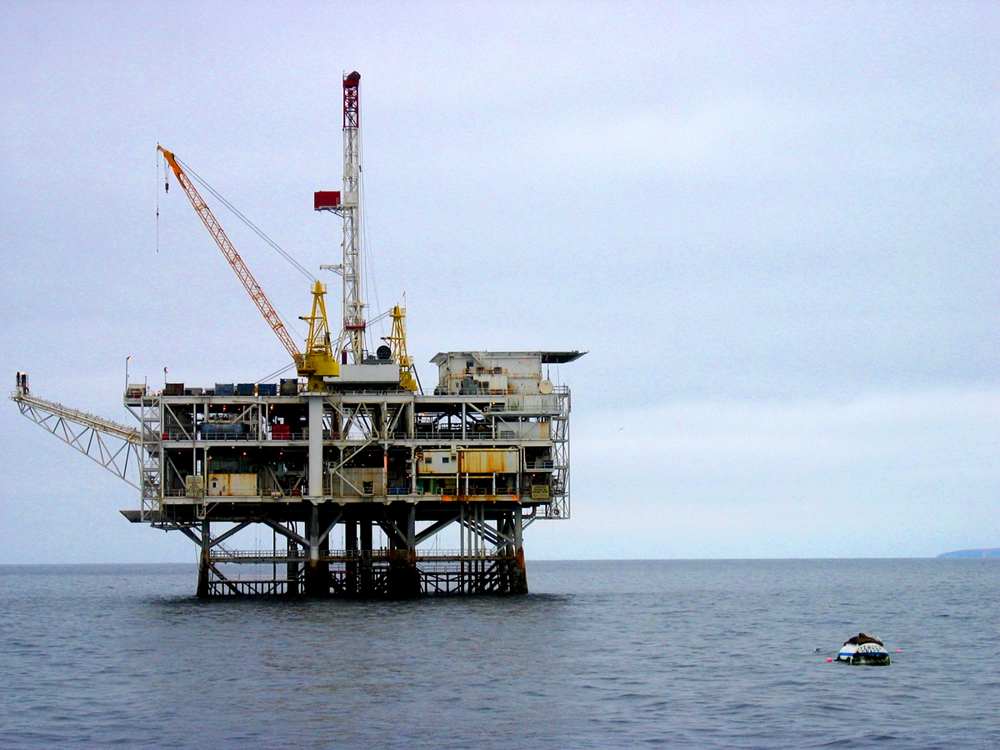 Expanse of ocean with large oil drilling platform on surface of water.