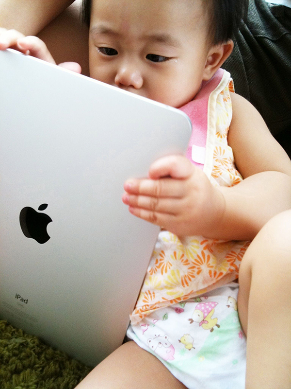 Very small child in diaper interacting with iPad