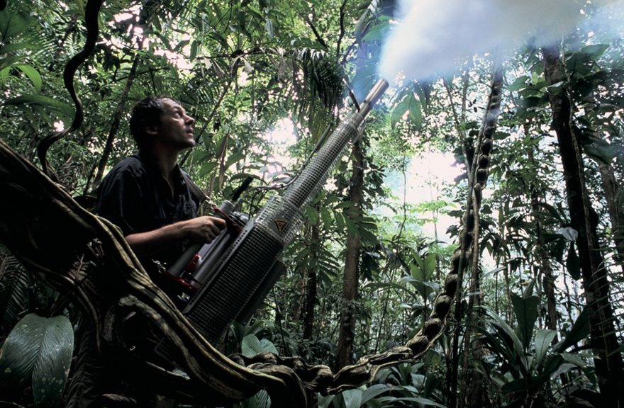 Man on forest floor shooting fog from a large gun into the air.