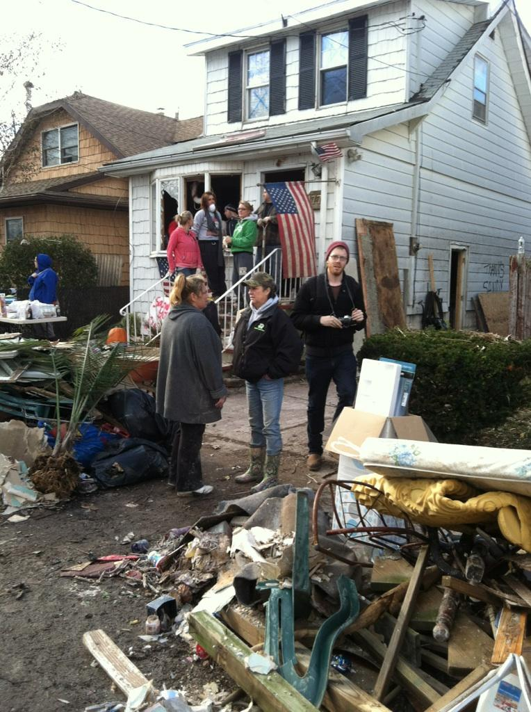 Many people gathered outside severely damaged home with debris cluttering yard