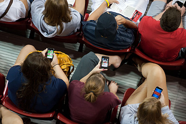Bird's-eye-view of crowd in indoor arena seats, three people in a row are using smartphones.