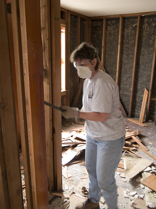 Air-masked person with crowbar in room showing studs with drywall completely removed