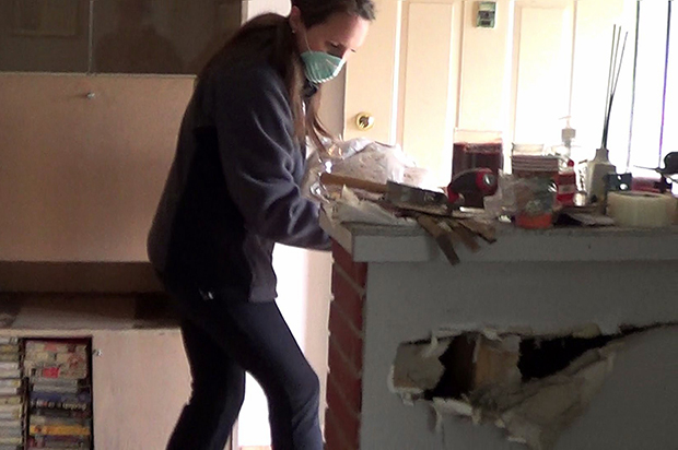 Air-masked person removing drywall in flood-damaged kitchen