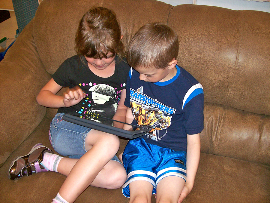 A young boy and girl seated on a couch, huddling over an iPad.