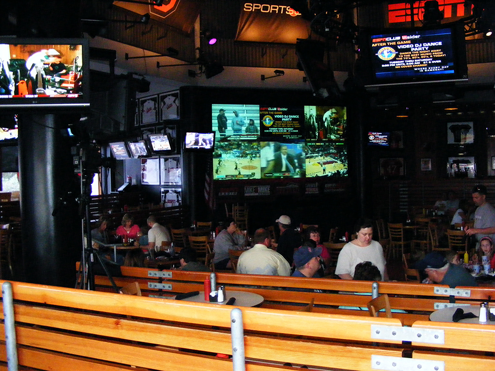 View of restaurant with at least 8 TV screens visible including huge one over bar.