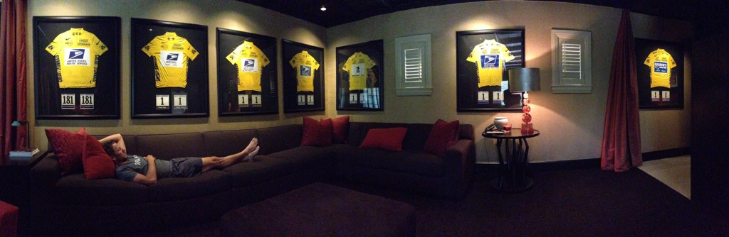 Seven yellow jerseys line the walls of a room with Lance Armstrong reclined on couch underneath them.