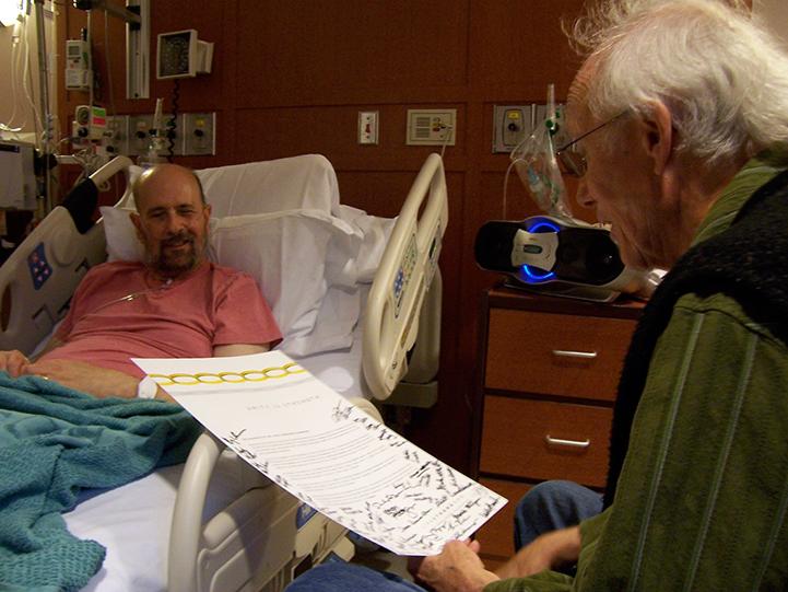 Man laying in hospital bed with head lifted while he listens to another man read from a piece of paper.
