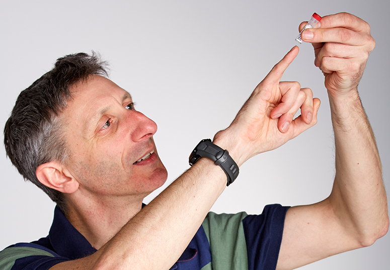 Male scientist holding pinky-sized vial up to the light.