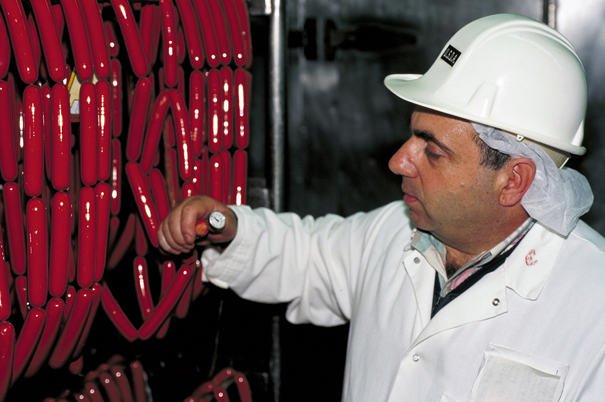 Man in white coat and white hardhat checks temperature of hot dogs hanging in production facility.