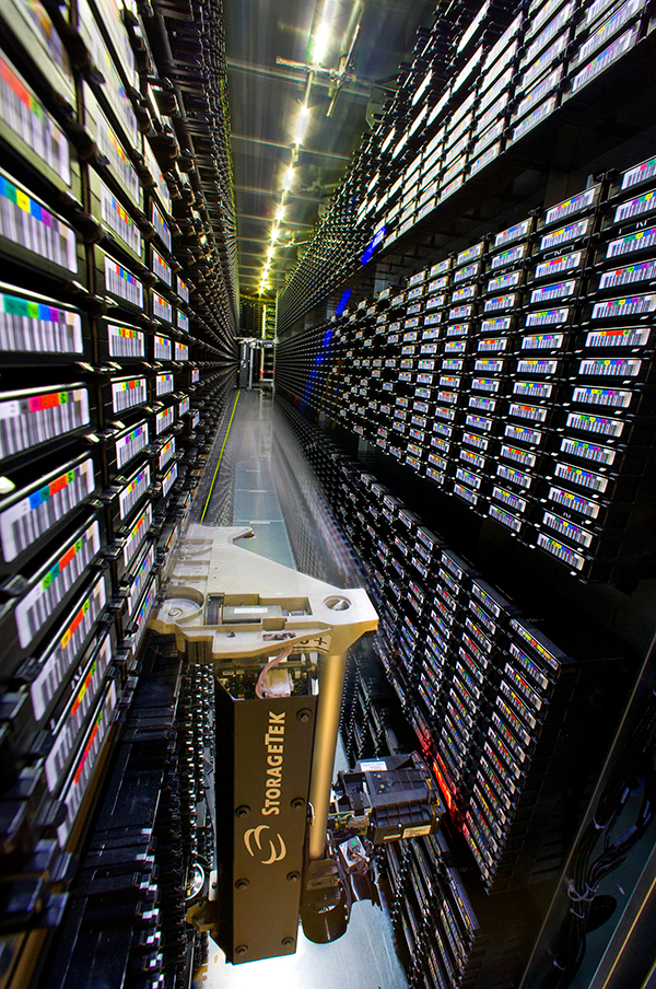 Bar codes are everywhere as robot traverses floor-to-ceiling shelves holding tape cartridges.
