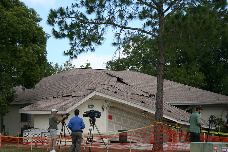 House that is partially caved into ground with large cracks through roof.