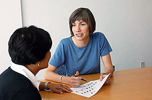 Counselor talks to visitor with genetic testing results in hand.