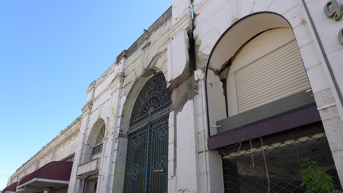 Building surrounded by fence has large crack in upper façade.