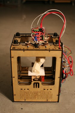 A orange box contains a white shape with many wires, and belts used to position ink-jet head.
