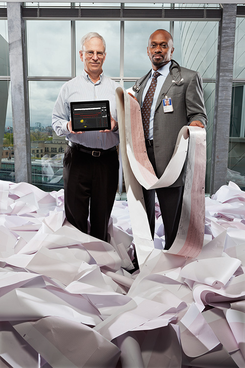 Two researchers stand, holding an iPad and a long scroll of electrocardiography diagram respectively