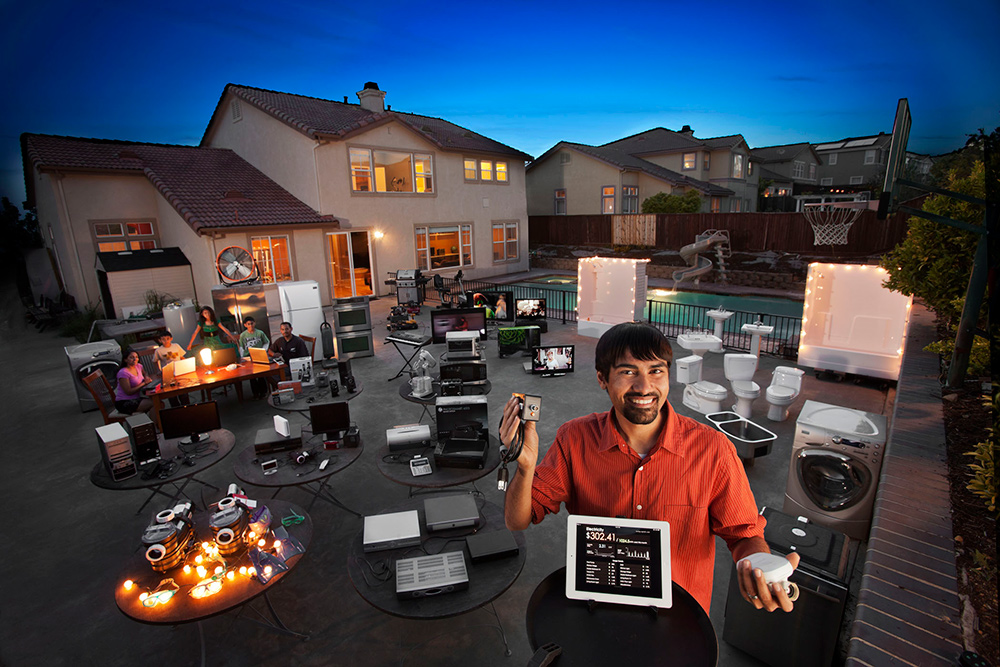 Holding a plugin, man smiles in backyard with electrical devices placed on tables and a lighted house behind him.