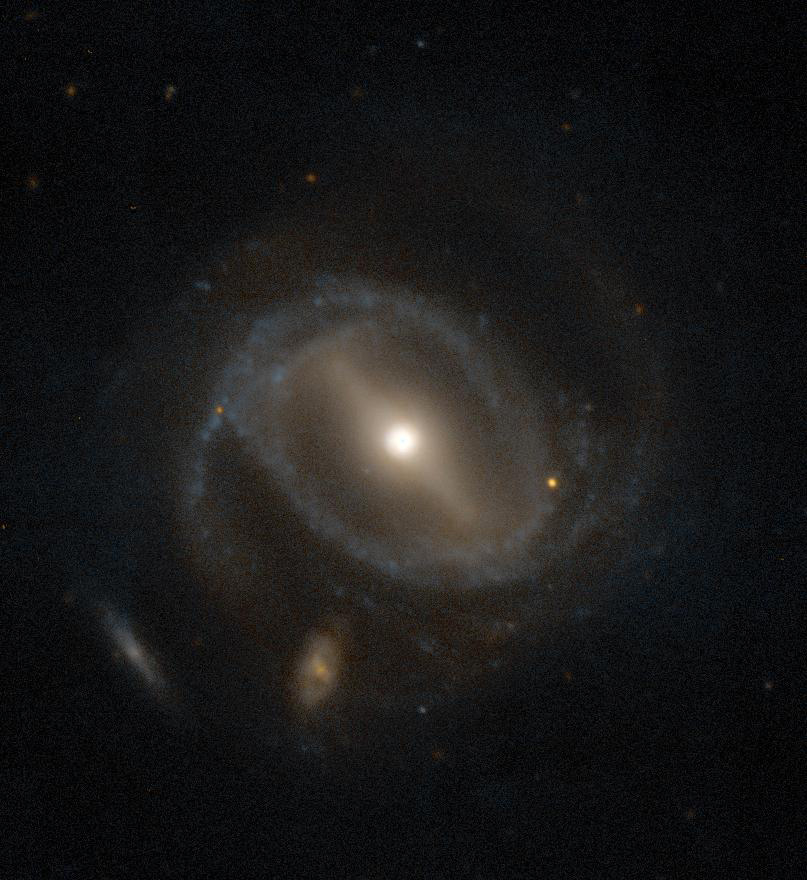 A big spiral galaxy with a small galaxy behind it