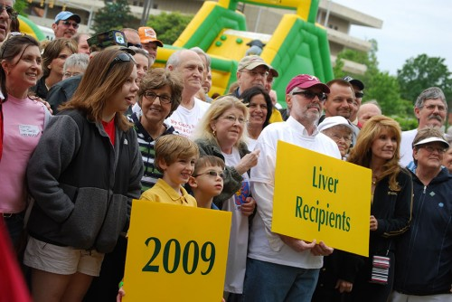 People gathered. An adult and two kids hold yellow boards saying 'liver recipients' and '2009'