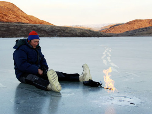 Man sits on ice in front of yellow flame, about 24 inches tall.