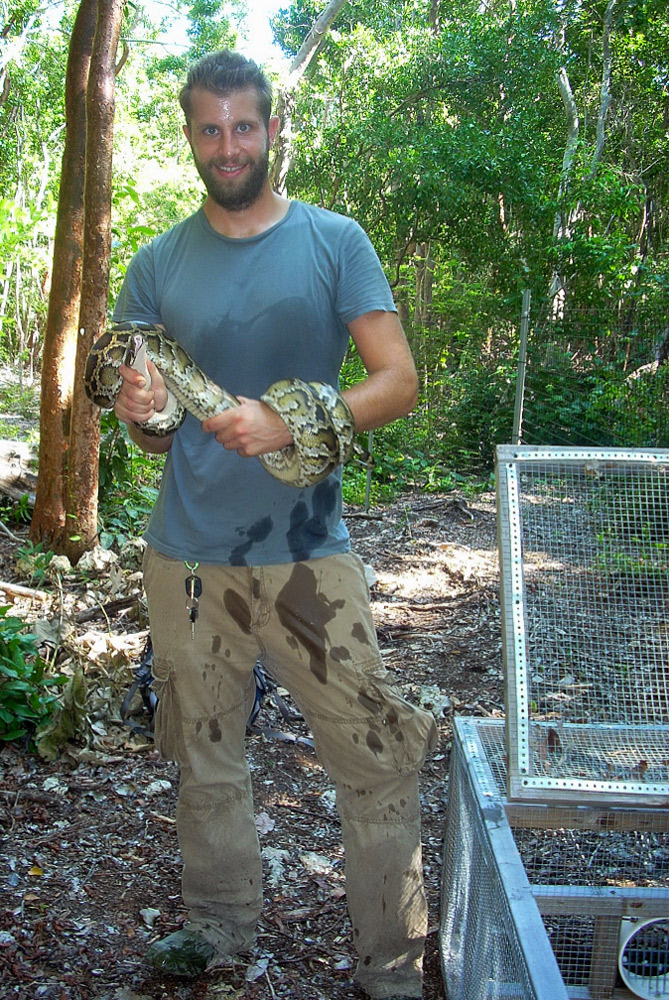 Man standing and smiling in forest, snake twisted around arms, open cage on ground next to him