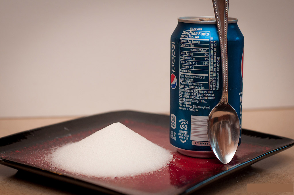 A can of Pepsi next to a small pile of white sugar. respectively.