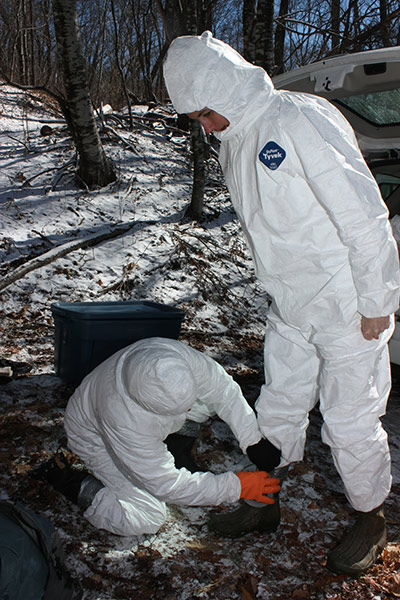 In woods covered with snow, a researcher is helping another researcher tape her rubber boots onto her white coverall suit.