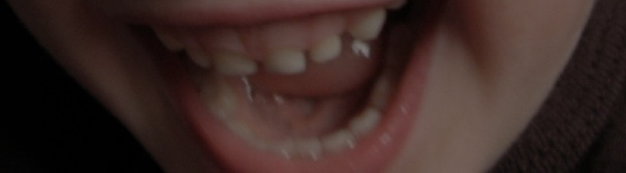 close-up of a young child's laughing mouth