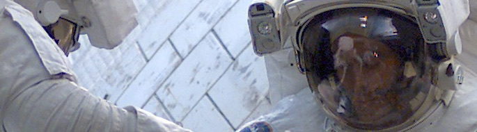 Photo close-up of astronaut's face with white shuttle surface behind him, and a 2nd astronaut nearby partially visible