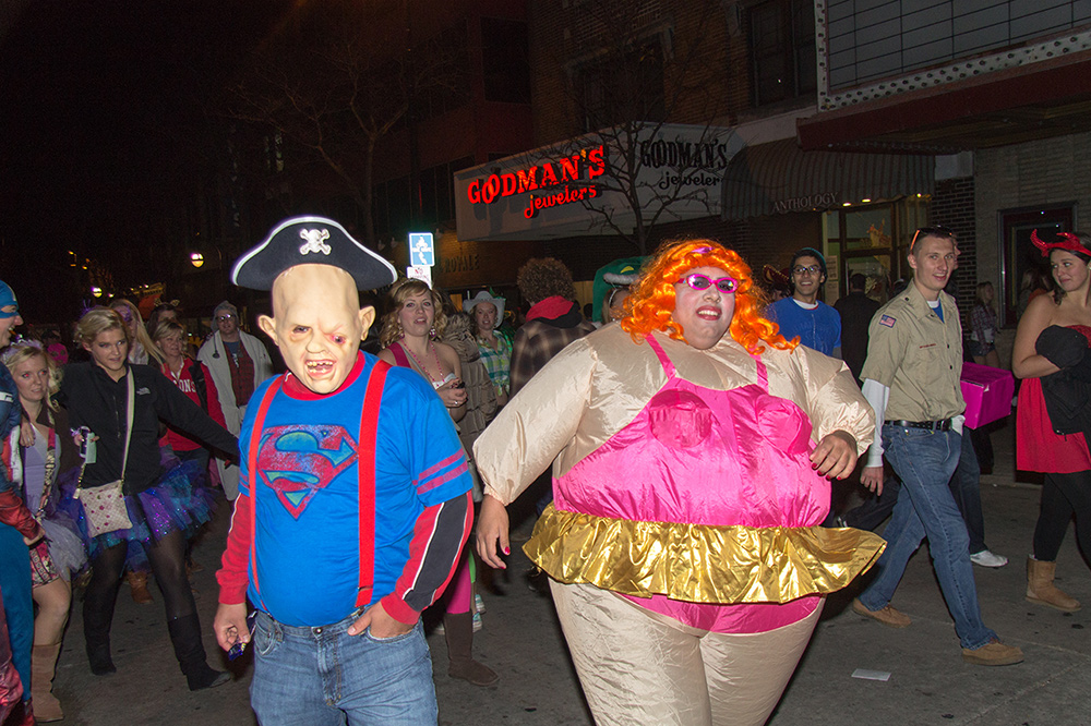Crowds of people dress in costumes walking in the street.