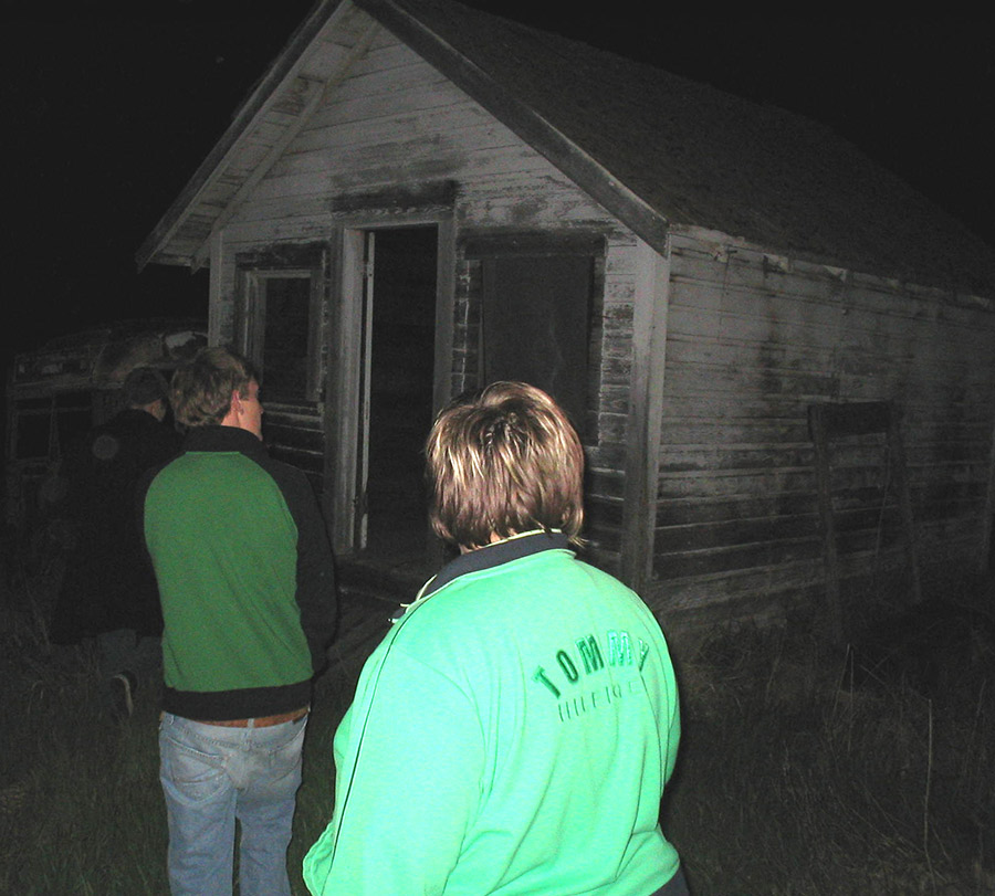 In the darkness, three people are approaching a desolate house.