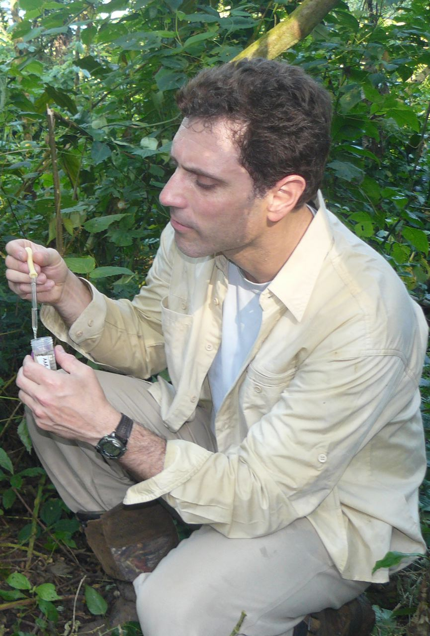 a male scientist squats down in bushes, holding test tube in left hand and dropper in right hand.