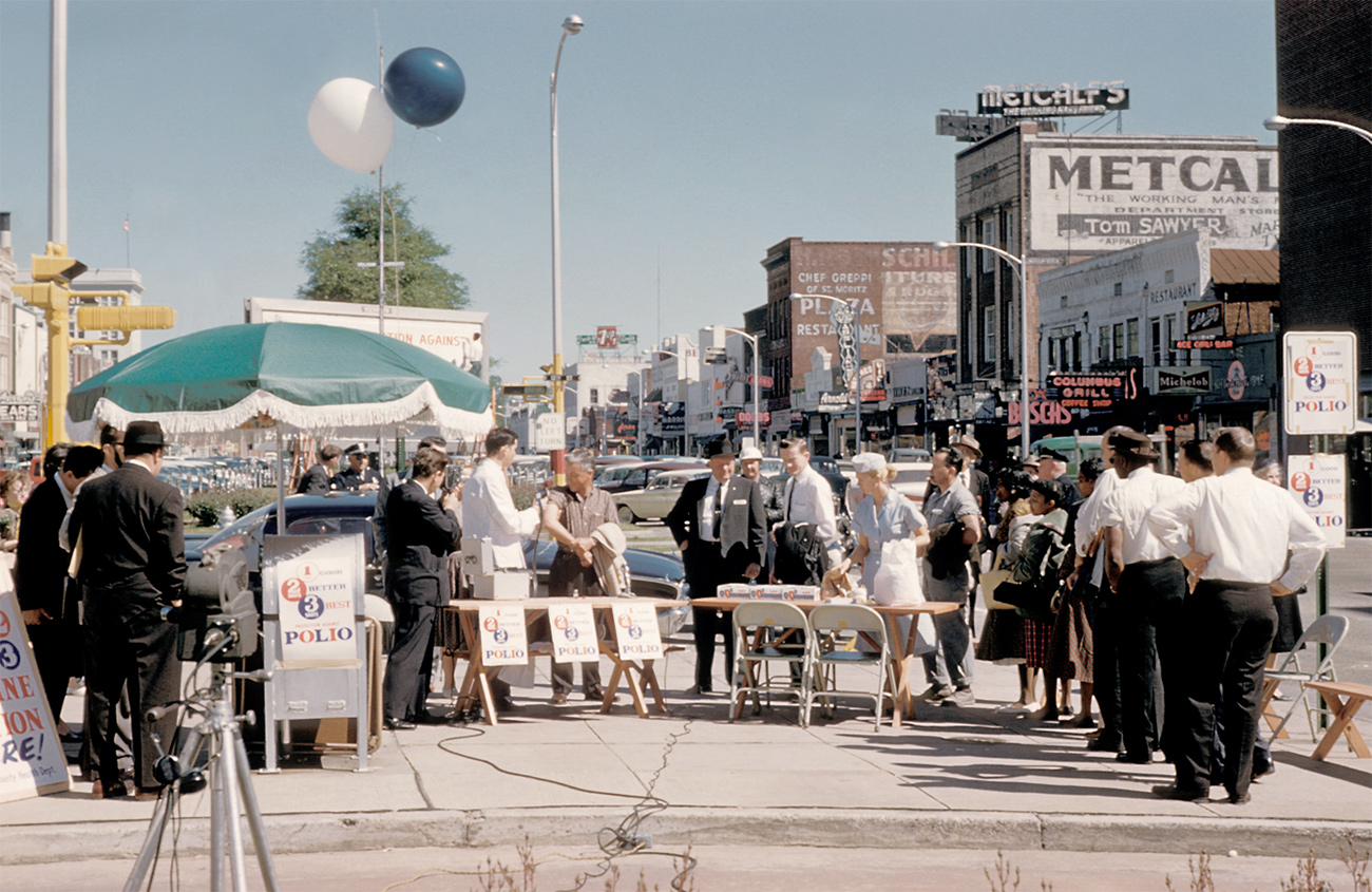 c. 1961 people wait in line for polio vaccine on sidewalk in downtown Colombus, Georgia. Men in suits and ties, women in dresses. Signs indicate public campaign, wooden tables and metal chairs