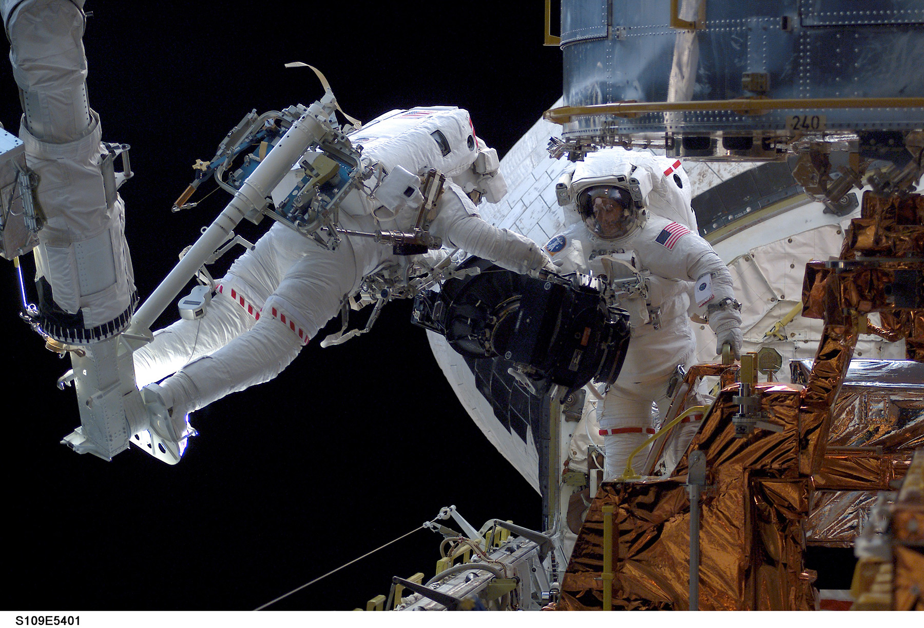 Two astronauts work in the payload bay of a space shuttle