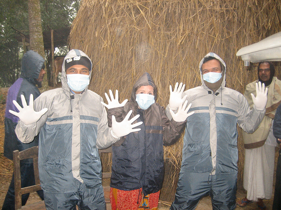 Three researchers standing in front of a hut, wearing hoodies, face masks and white gloves