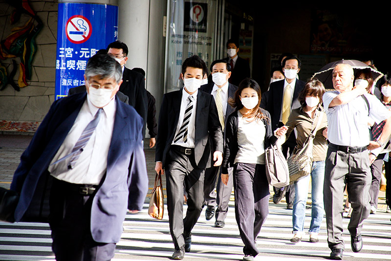 People walking out of a subway station, wearing white face masks