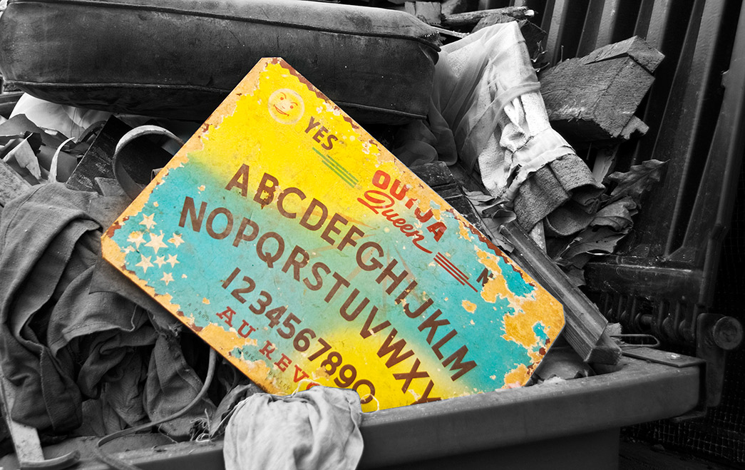 A colorful ouija board in a garbage bin