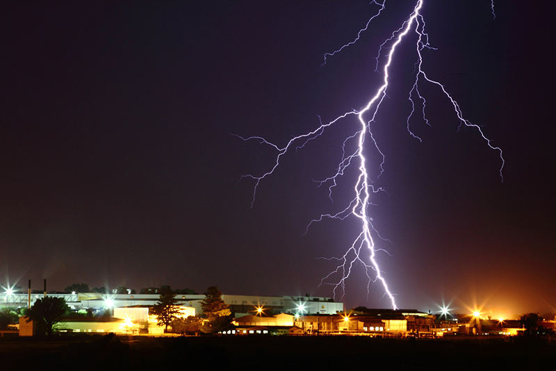 lightning in night sky touches down on lighted city