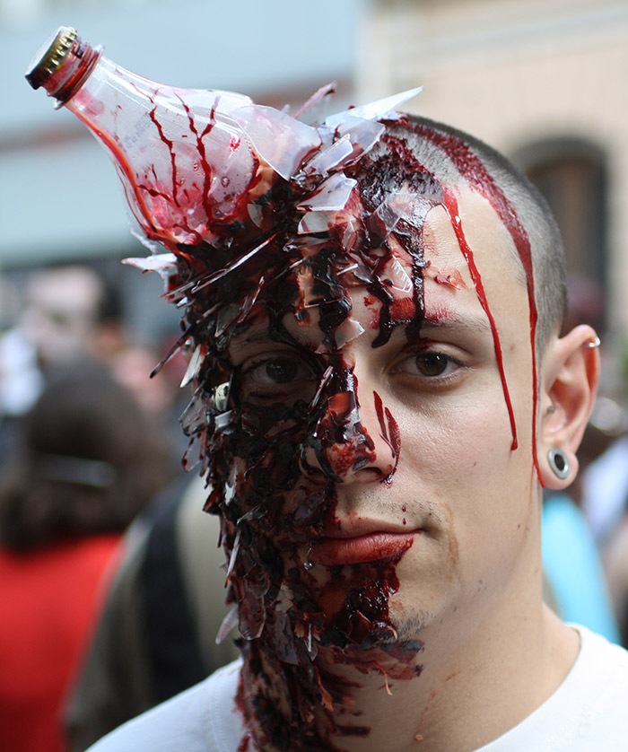 A young man with a broken bottle stuck to his head and blood-like juice running through his face