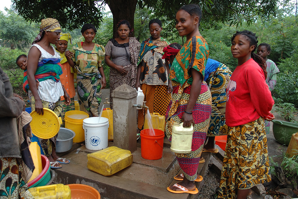 A group of African women dressed in colorful garments filling their buckets with water from a fountain