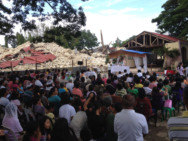People gathering in an open area, with clerks conducting ceremony in the front and collapsed houses in the background