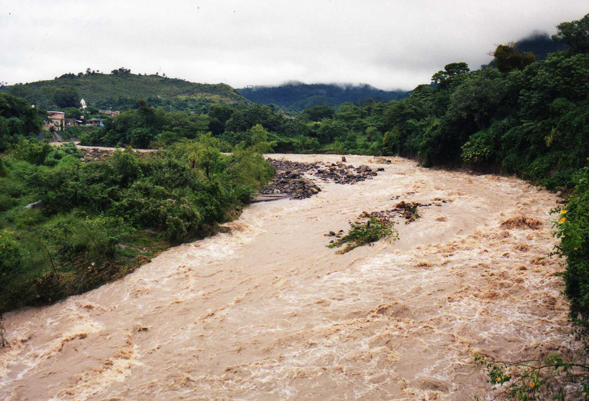 Flooded river running through villages and jungle
