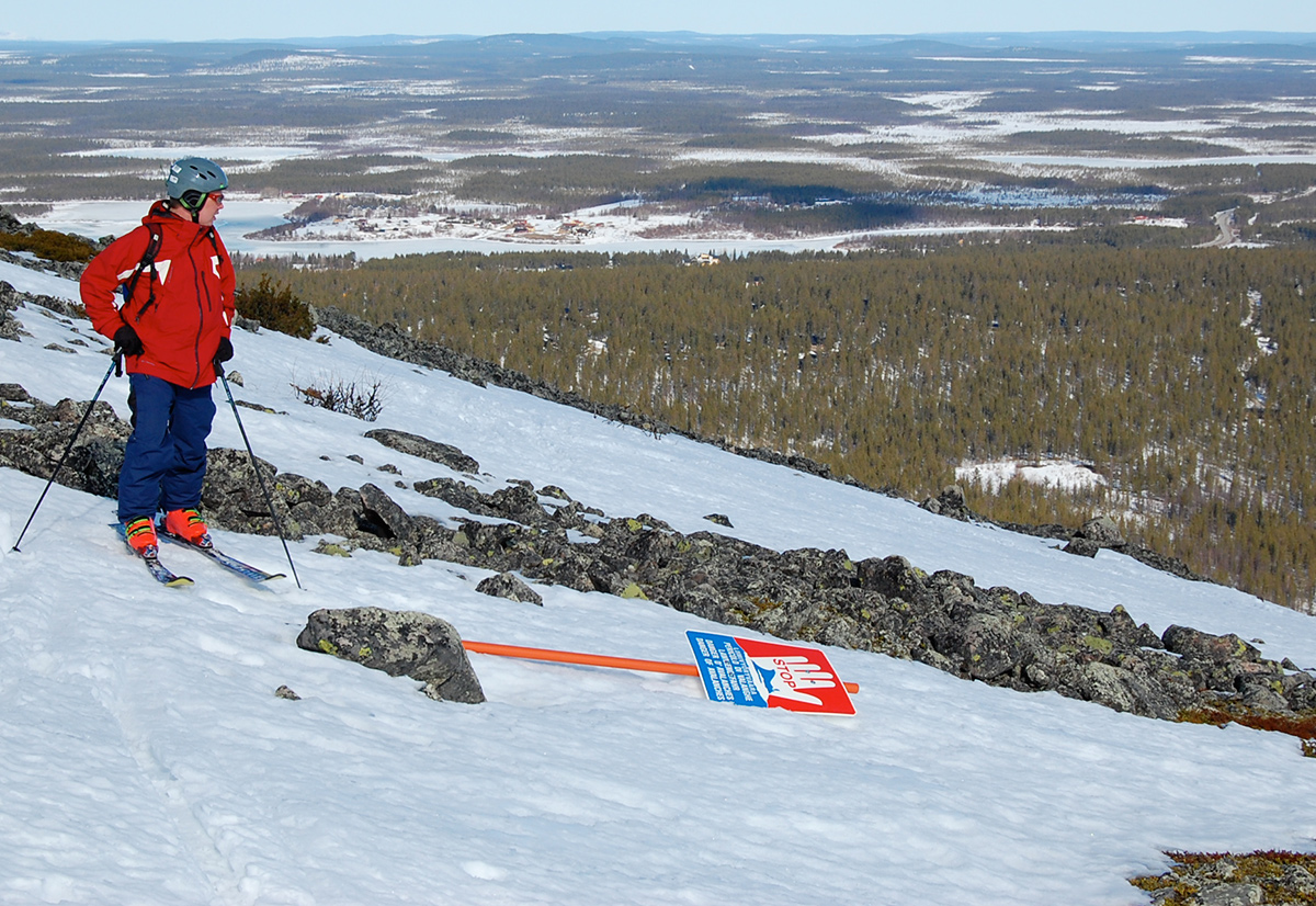 a skier in red is looking at a downhill ski trail, where many rocks crop out.