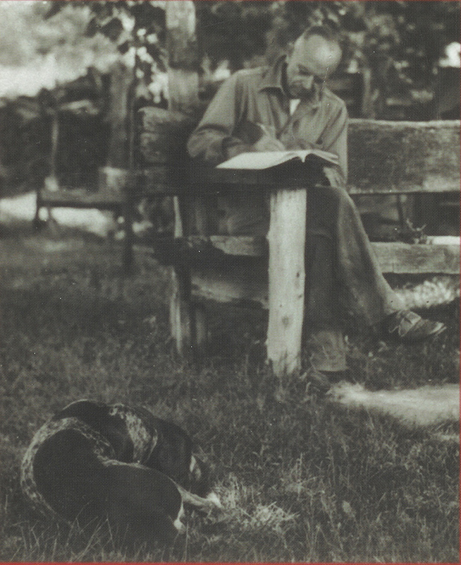 In black-and-white photo, man sits on outdoor bench, writing in journal. Dog sleeps at his feet.