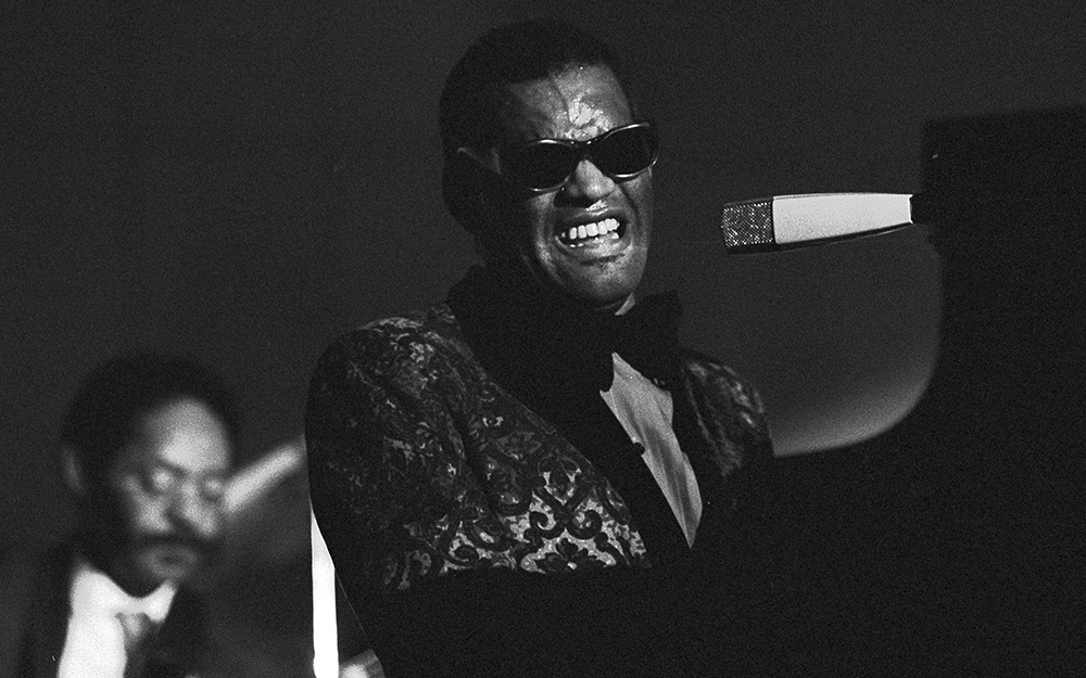 Ray plays/sings into microphone while seated at piano. Face grimaces with effort. Wears iconic black sunglasses