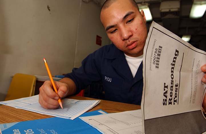 a soldier in blue flipping over the exam papers and writing down the answers on a separate sheet